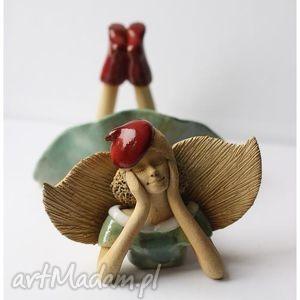 hand-made ceramika anioł leżący w czerwonej beretce